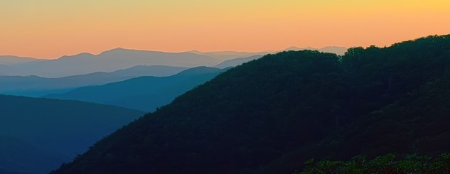 sunset over the appalachian mountains the mountains are blue and the sky is a soft orange.